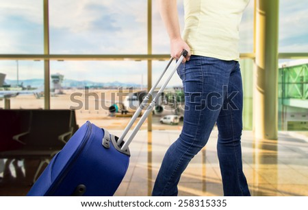 woman walking travel bag by an international airport - stock photo