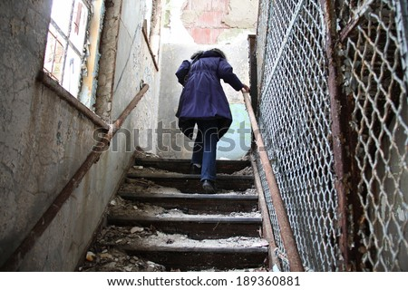 woman walking up dangerous steps in an abandon mental institution - stock photo