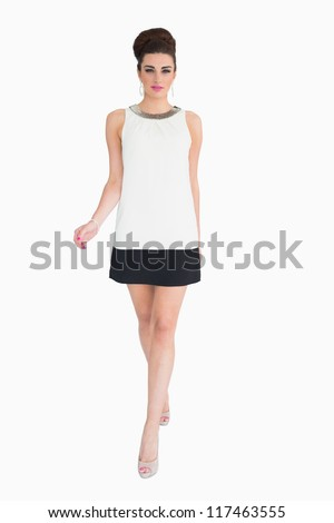 Woman walking while wearing a glamorous dress in the mod style - stock photo