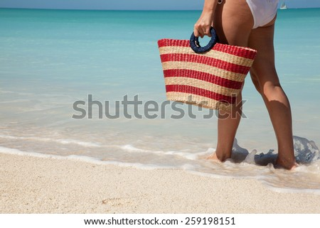 woman walking with bag at white sand beach