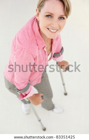 Woman walking with crutches - stock photo