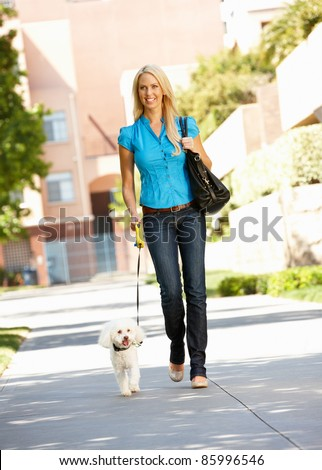 Woman walking with dog in city street - stock photo