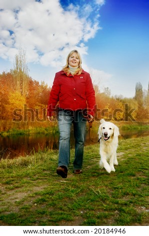 woman walking with her golden retriever dog in autumn nature