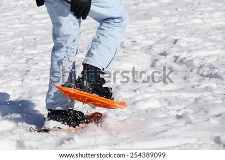 woman walking with snowshoes on freshly-fallen snow - stock photo