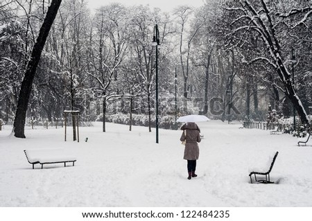 woman walking with umbrella in winter snowy landscape with trees - stock photo