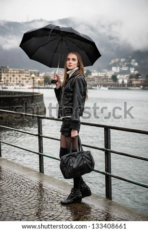 Woman walking with umbrella under the rain - stock photo