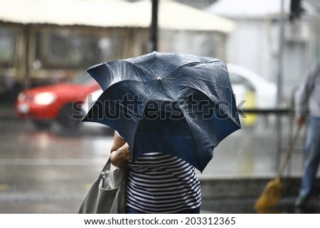 Woman walking with umbrellas in the rain - stock photo