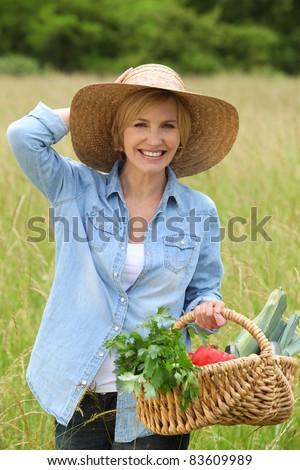 Woman walking with vegetable basket - stock photo