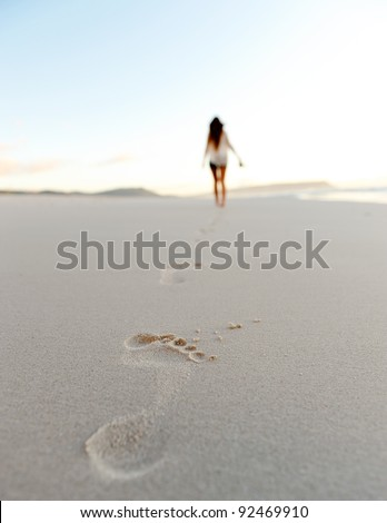 woman walks alone on a deserted beach, solitude, serene, lonely concept. carefree vacation in nature - stock photo