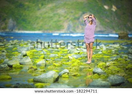 woman walks alone on a green reef - stock photo