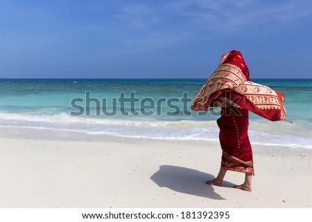 Woman walks along the white beach enjoying the breeze wearing an Indian Saree. - stock photo