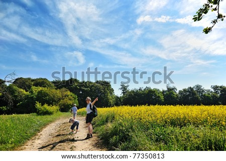 woman wandering with two boys (her children) on a path near the forest - stock photo