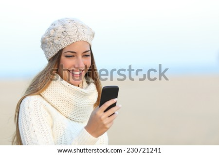 Woman warmly clothed in winter using a smart phone on the beach - stock photo