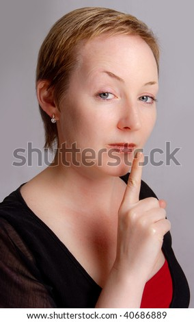 Woman warning to shut up with a serous expression - stock photo