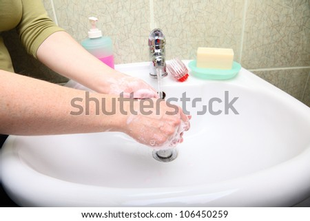 Woman wash red soapy hands in bathroom soap - stock photo