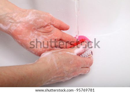 Woman wash red soapy hands in bathroom soap nail brush person scrubbing nails - stock photo