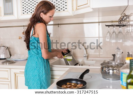 Woman washing a cheese grater under running water in the kitchen sink after grating cheddar cheese for the recipe she is preparing - stock photo
