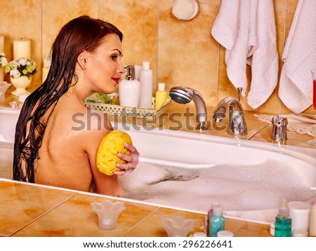 Woman washing and relaxing at water in bubble bath. - stock photo