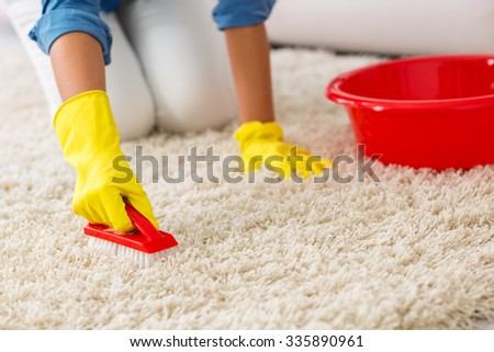 Woman washing carpet with brush at home - stock photo