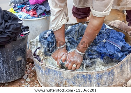 Woman washing cloths by hand in the Draa Valley, Morocco. - stock photo