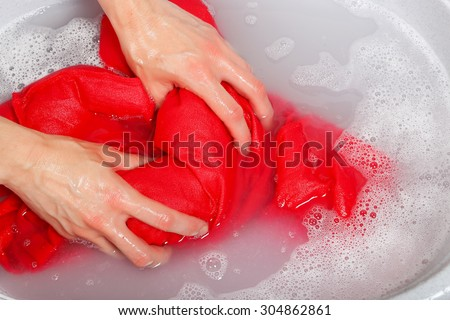 woman washing delicate clothes by hands in plastic tub - stock photo