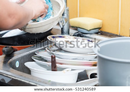 Woman washing dish in the kitchen after dinner