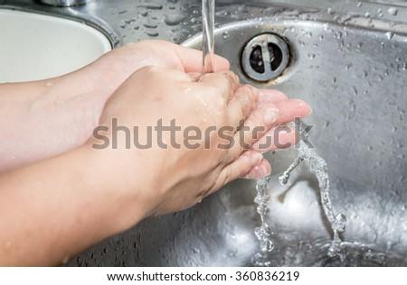 Woman washing hand under running - stock photo