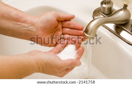 woman washing hand under running water white sink chrome spout - stock photo