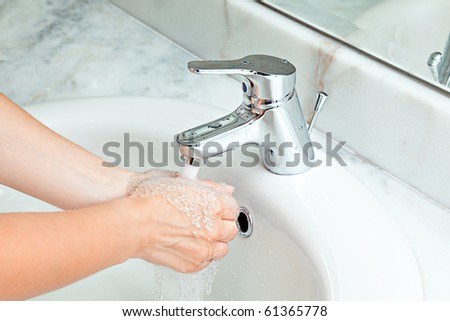 woman washing hands at marble bathroom