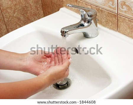 Woman washing hands with soap in bathroom - stock photo