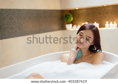 woman washing herself with sponge at bath with foam. Woman at bathroom. - stock photo