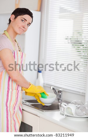 Woman washing the dishes looking into the camera in the kitchen