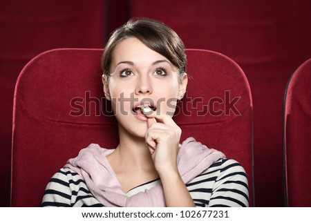 Woman watching a movie with enthusiasm - stock photo