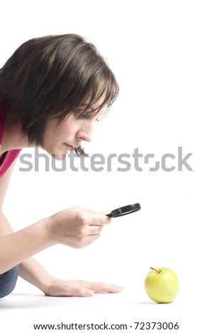 Woman watching green apple with a magnifying glass - stock photo
