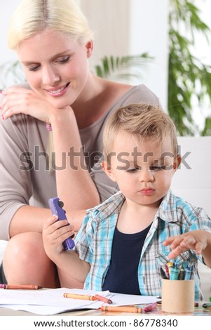 Woman watching her son playing - stock photo