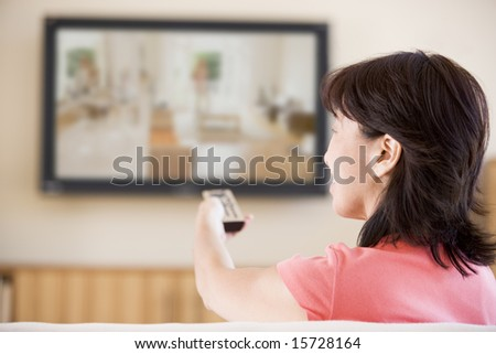 Woman watching television using remote control - stock photo