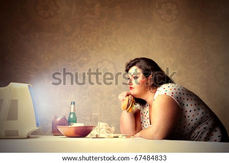 Woman watching television while dining with a hamburger - stock photo