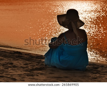 Woman watching the light playing on the sea - silhouette - stock photo