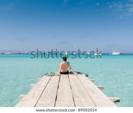 Woman watching the sea sitting on a jetty - stock photo
