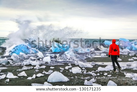 Woman watching waves crash against icebergs at Jokulsarlon glacial lagoon near Vatnajokull National Park, southeast Iceland - stock photo
