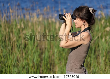 woman watching wildlife with binoculars in swamp area
