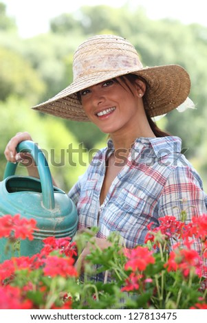 Woman watering her plants on a sunny spring day - stock photo