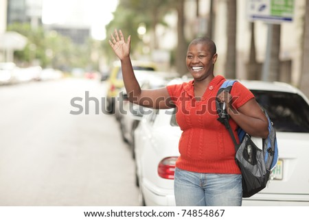 Woman waving on the street - stock photo
