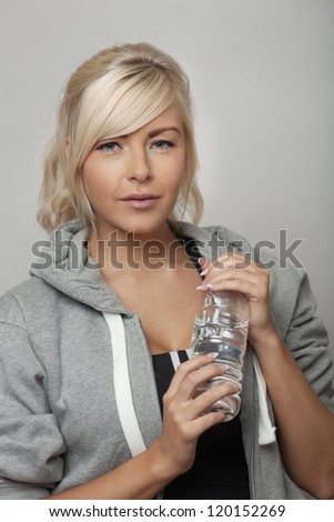 woman wear a hoodie tracksuits holding a bottle of water - stock photo