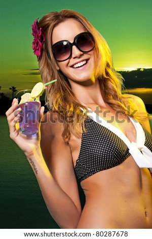 Woman wearing a bikini in a swimming pool holding a colorful cocktail with an umbrella and straw. - stock photo