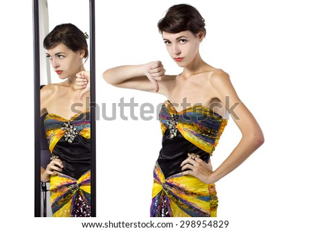 Woman wearing a dress with her thumbs down while looking at a mirror.  She looks like she dislikes the outfit she is trying on. She is a fashion snob. - stock photo