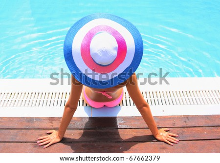 Woman wearing a hat in a swimming pool - stock photo