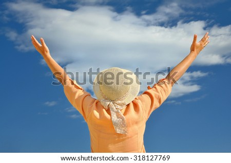 Woman wearing a hat with hands up looking at the sky