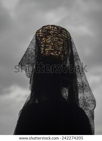 Woman wearing a headdress of black Spanish lace lifted high on a traditional comb standing with her back to the camera against a cloudy grey sky during a Holy Week in Andalucia, Spain - stock photo