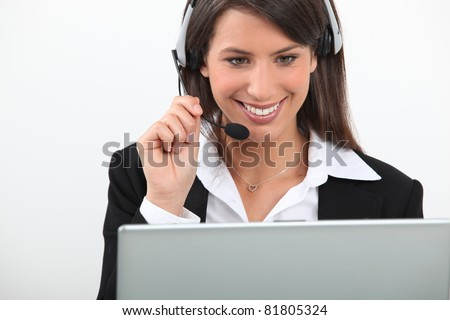 Woman wearing a headset sitting at a laptop computer - stock photo